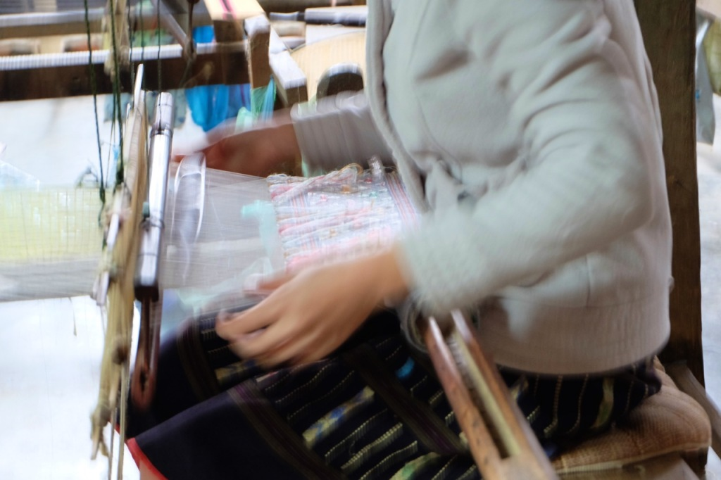 Hands flying over the loom